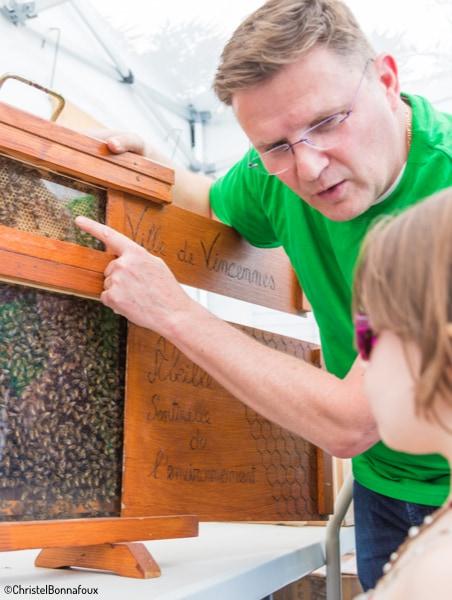 Homme qui explique le fonctionnement d'une ruche