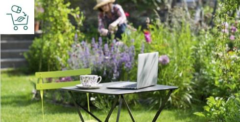 Petite table de jardin avec un ordinateur et femme jardinant en arrière-plan